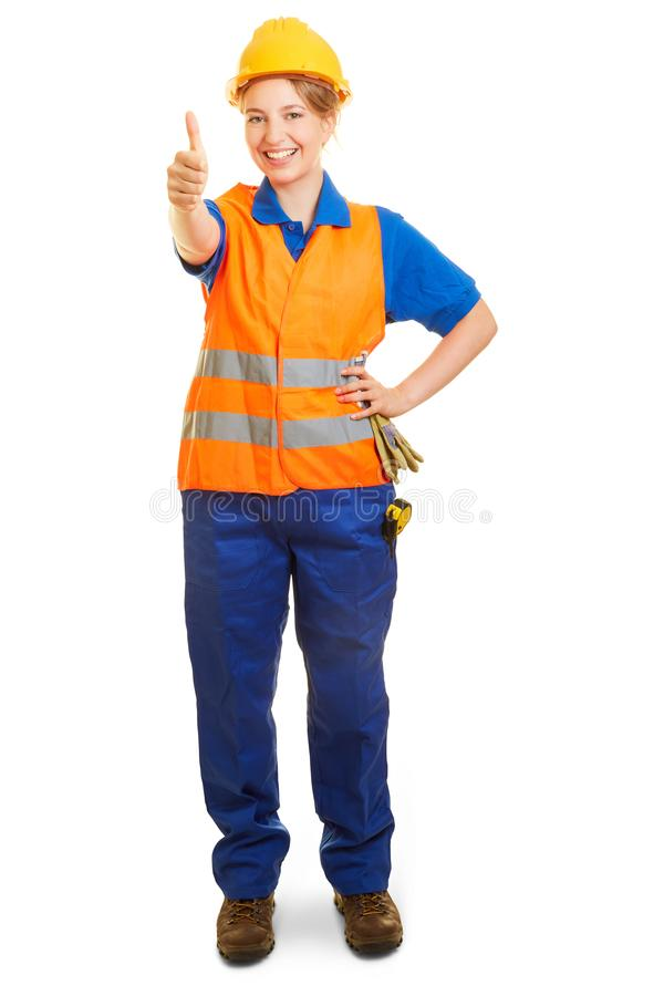 Woman as a road builder keeps thumbs up stock image