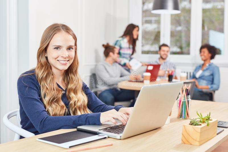 Young woman as trainee is working on laptop PC. Young women as apprentice or trainee working on laptop in an office community royalty free stock images