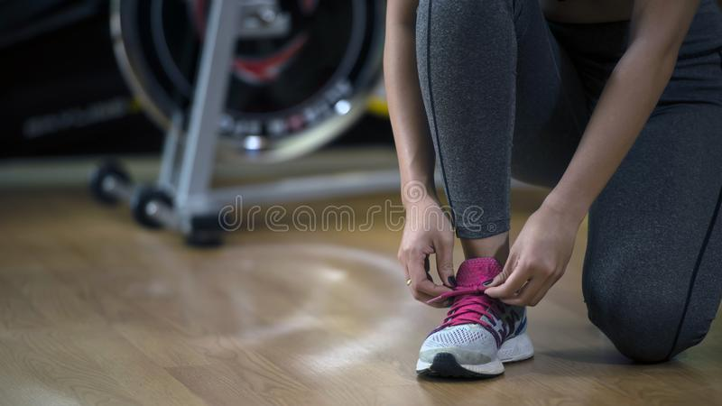 Young woman asian knelt down to do up his shoelaces at fitness g. Ym after running exercise workout for cardio and muscle building; ; healthy lifestyle royalty free stock images