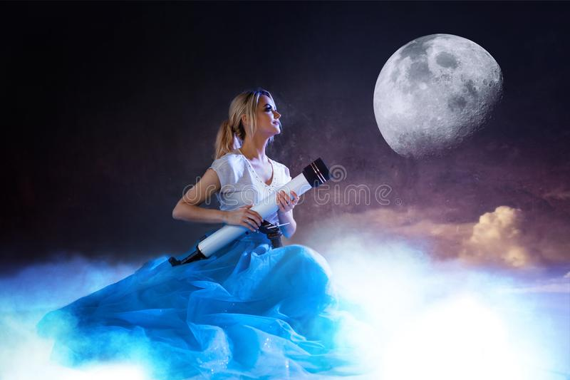Young woman astronomer, dreamer. Girl sitting on the clouds with a telescope in hands. The moon in the starry sky royalty free stock photo