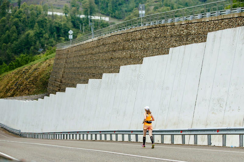 Young woman athlete in compression socks running downhill stock photography