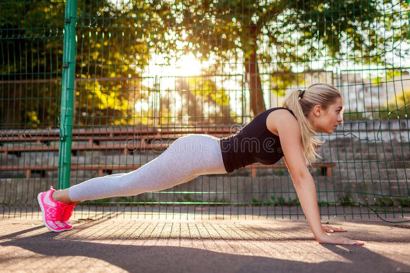 Young woman athlete doing push-ups on sportsground in summer. Plank. Healthy lifestyle. Morning exercises. Young woman athlete doing push-ups on sportsground in royalty free stock photo