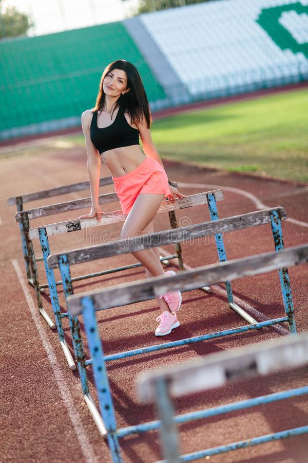 Young brunette woman athlete on stadium sporty lifestyle standing on track posing near the barriers running jumping to camera royalty free stock photos