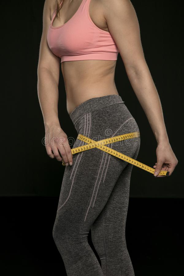 Young woman with an athletic body uses a measuring tape royalty free stock photography
