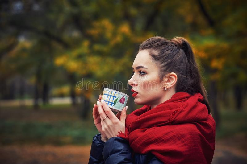 A young woman in an autumn city Park holding a Cup with a hot drink royalty free stock photography