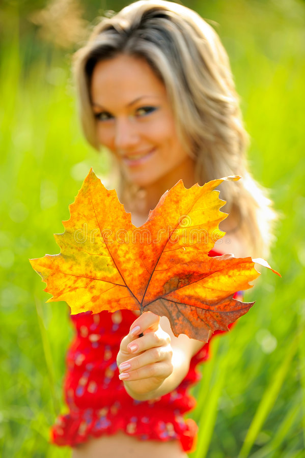 Young woman with autumn leaf royalty free stock image