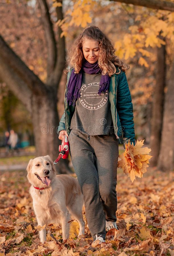 Portrait of a young woman with dog on golden autumn walk. royalty free stock photo