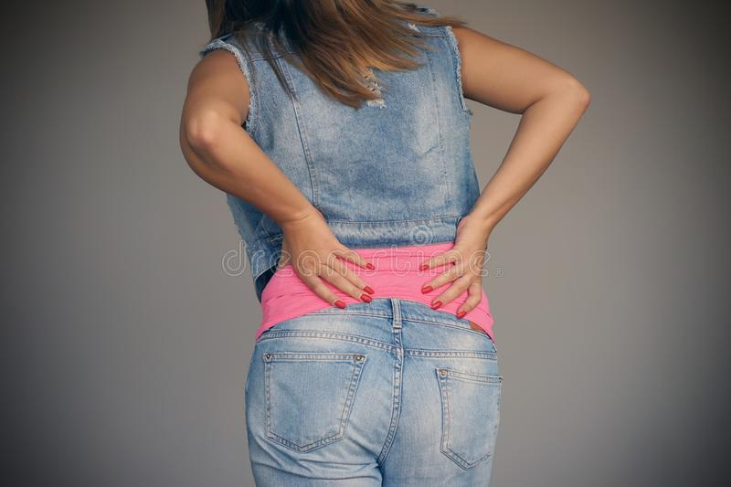 Woman, pain at lower back. Young woman with back ache clasping her hand to her lower back. Close-up view of a young woman with pain in kidneys isolated on a gray stock image