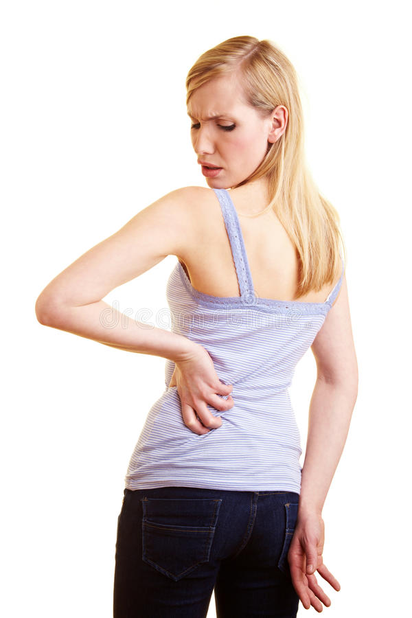 Young woman with back pain. Young blonde woman touching her aching back stock photography