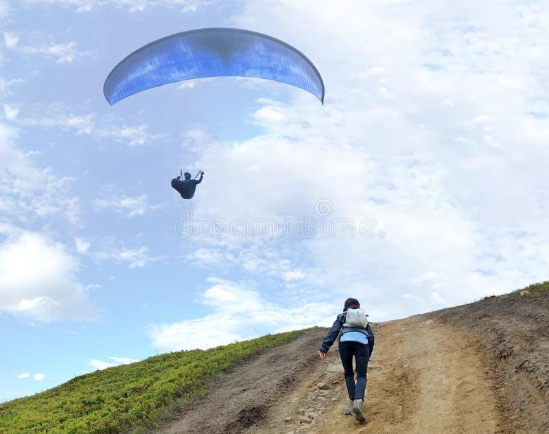 A young woman climbs up a mountain to meet a paraglider hovering in the air royalty free stock images