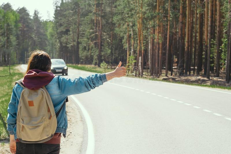 Woman with backpack  hitchhiking on the road. Young woman with backpack  hitchhiking on the road stock photos