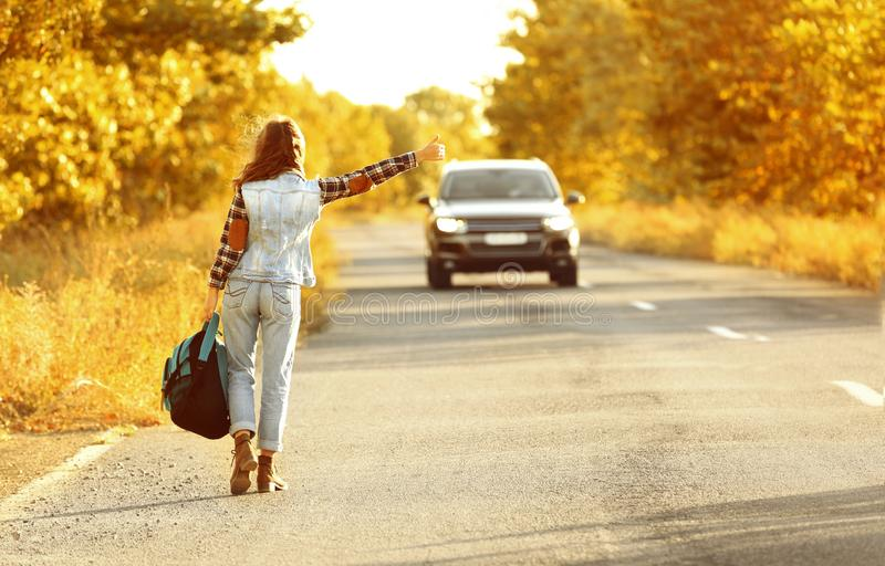 Young woman with backpack hitchhiking royalty free stock photos