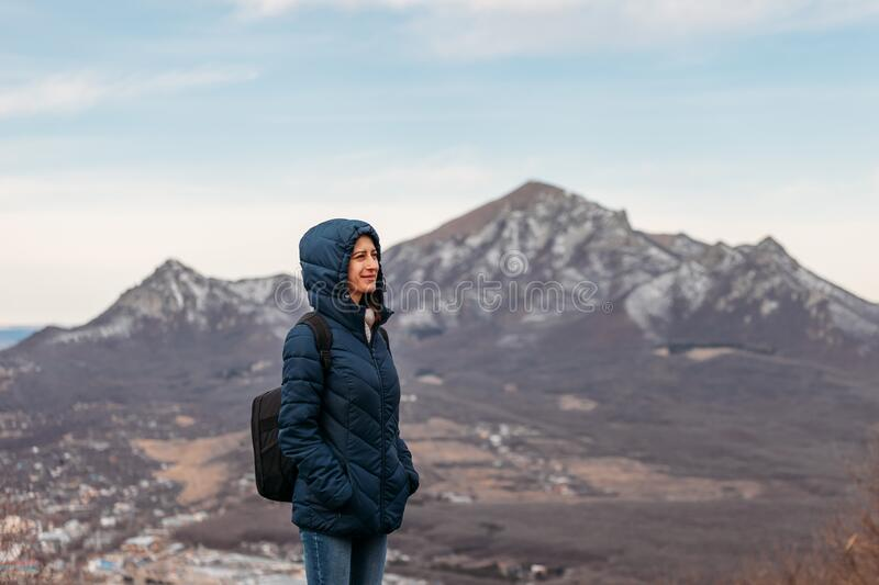 Young woman with backpack on mountain top on mountain background.  stock image