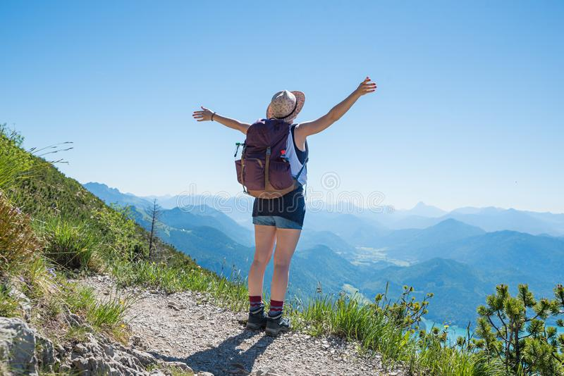 Young woman with outstretched arms enjoy lookout at herzogstand mountain stock image