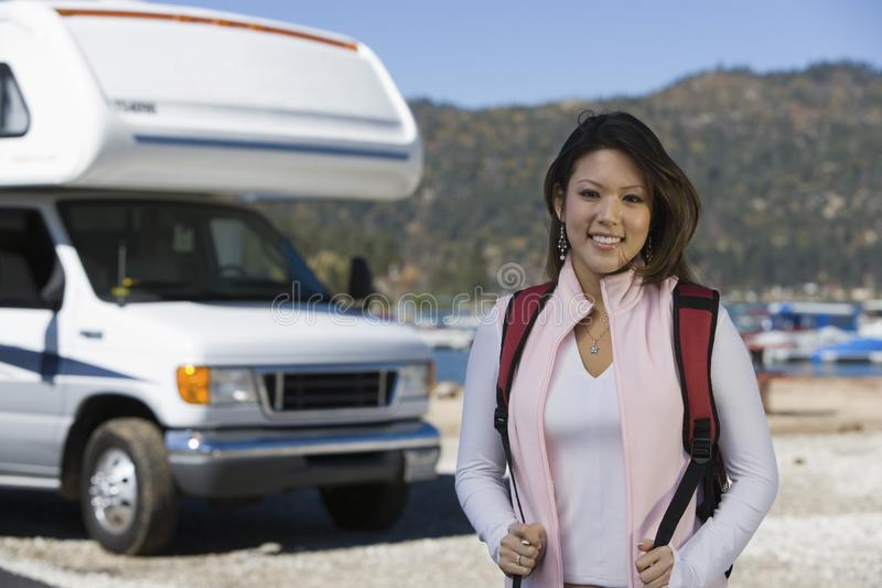 Young woman with backpack by RV at lake stock photos