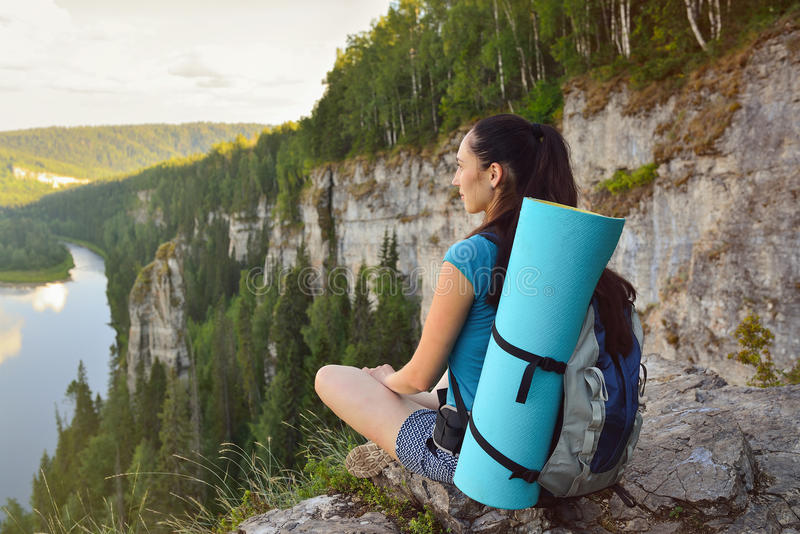 Young woman with backpack sitting on cliff's edge at high mountain stock photo