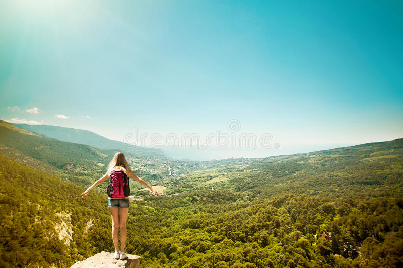 Young woman with backpack standing on cliff edge. Raised hands. Landscape composition. Happiness, lifestyle concept stock photography