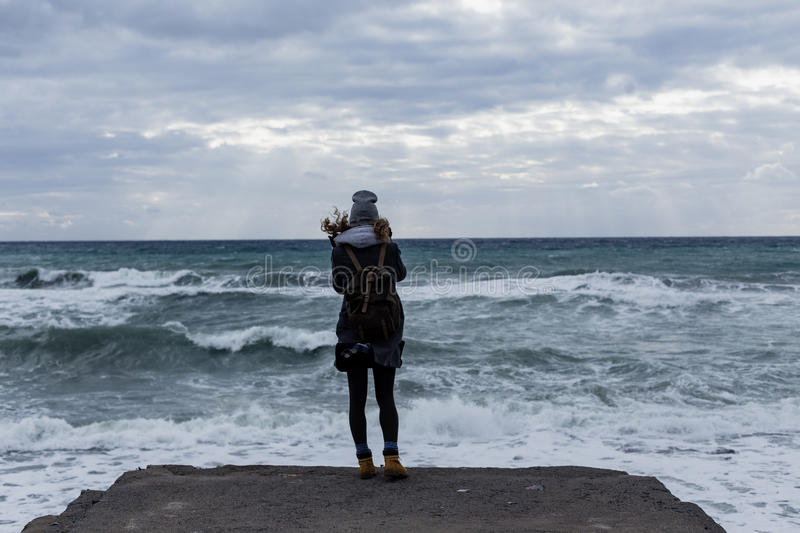 Young woman with backpack standing on cliff`s edge. And looking to a sky with raised hands royalty free stock photo