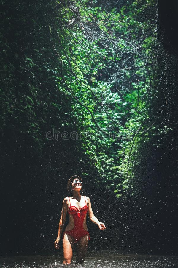 Young woman backpacker looking at the waterfall in jungles. Ecotourism concept image travel girl. Bali island. stock images