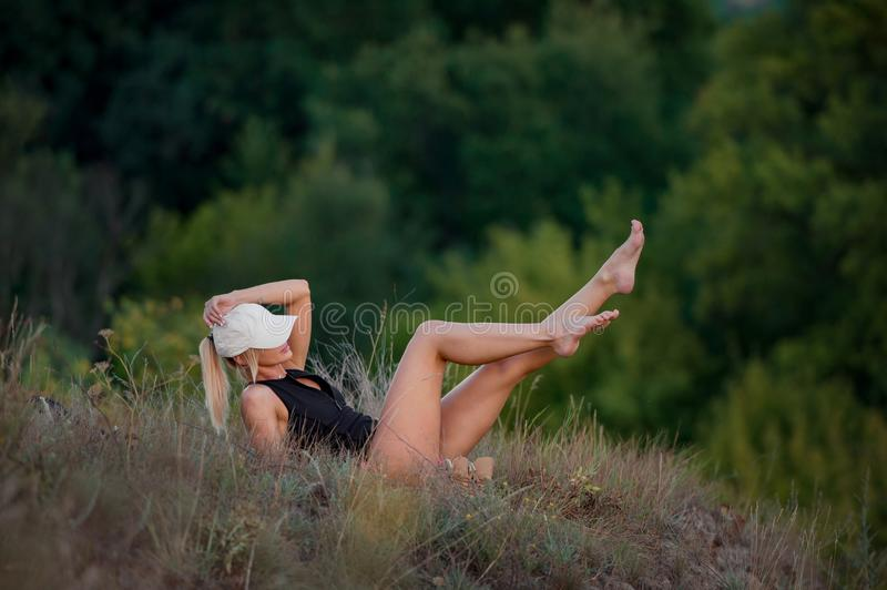 Young woman backpacker, lying on top of the hill, posing, showing her legs and enjoying the nature. Forest background royalty free stock photos