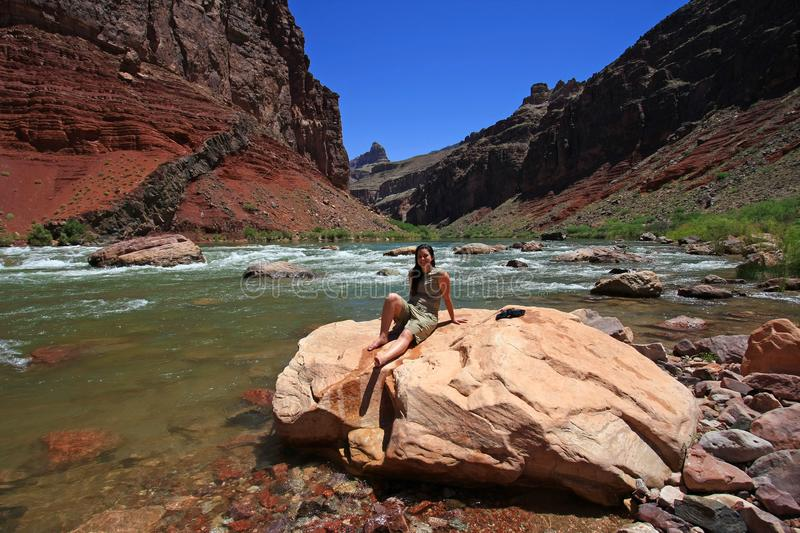 Young woman backpacker resting by the Colorado River in the Grand Canyon. Young woman backpacker resting by the Colorado River at Hance Rapids in Grand Canyon stock image