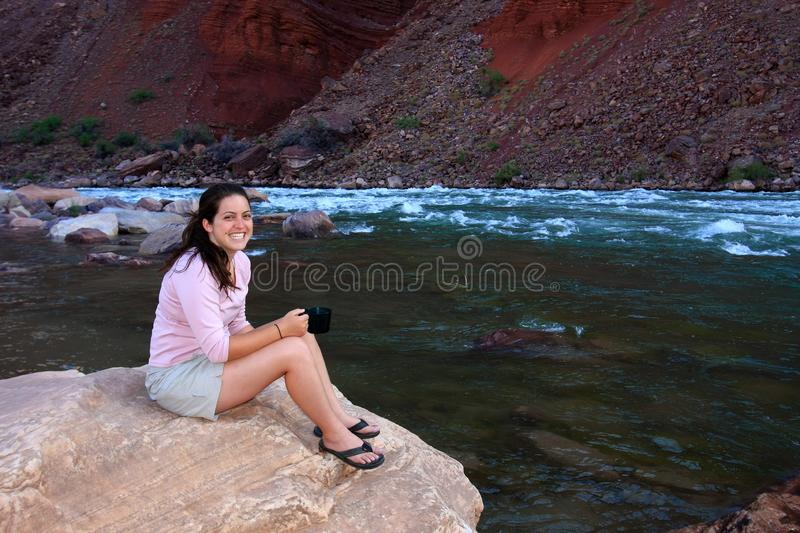 Young woman backpacker resting by Hance Rapids in the Grand Canyon. Young woman backpacker resting on the boulders by Hance Rapids in Grand Canyon National Park stock image