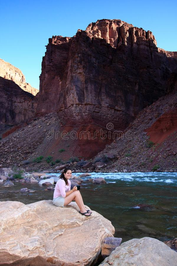 Young woman backpacker resting by Hance Rapids in the Grand Canyon. Young woman backpacker resting on the boulders by Hance Rapids in Grand Canyon National Park royalty free stock photos