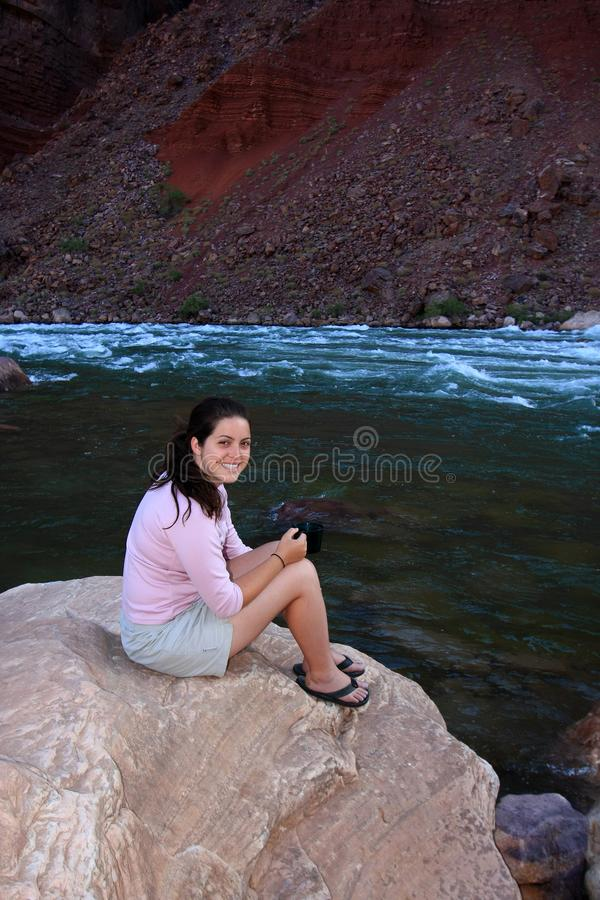 Young woman backpacker resting by Hance Rapids in the Grand Canyon. Young woman backpacker resting on the boulders by Hance Rapids in Grand Canyon National Park royalty free stock image