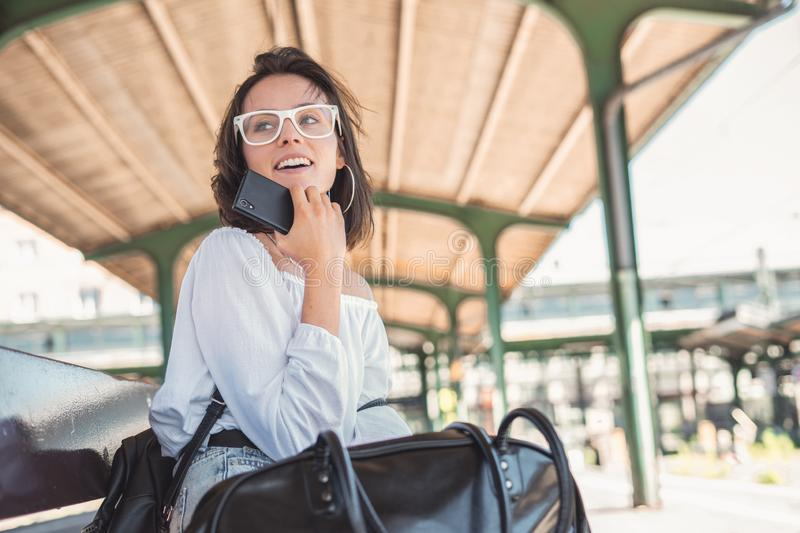 Young woman with bag and backpack waiting to train. stock photography