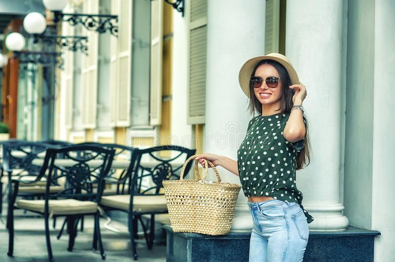Young woman with bag and hat on a walk in the city stock image