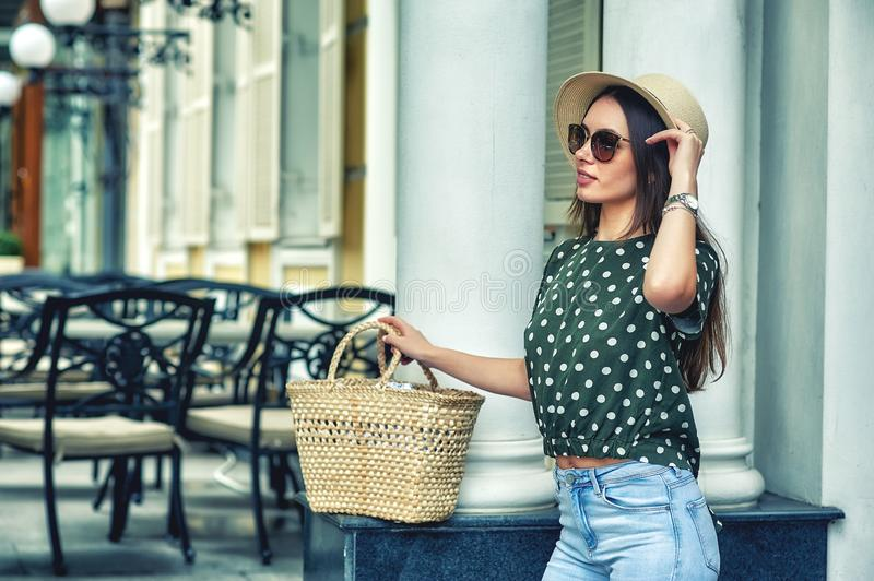 Young woman with bag and hat on a walk in the city stock photography