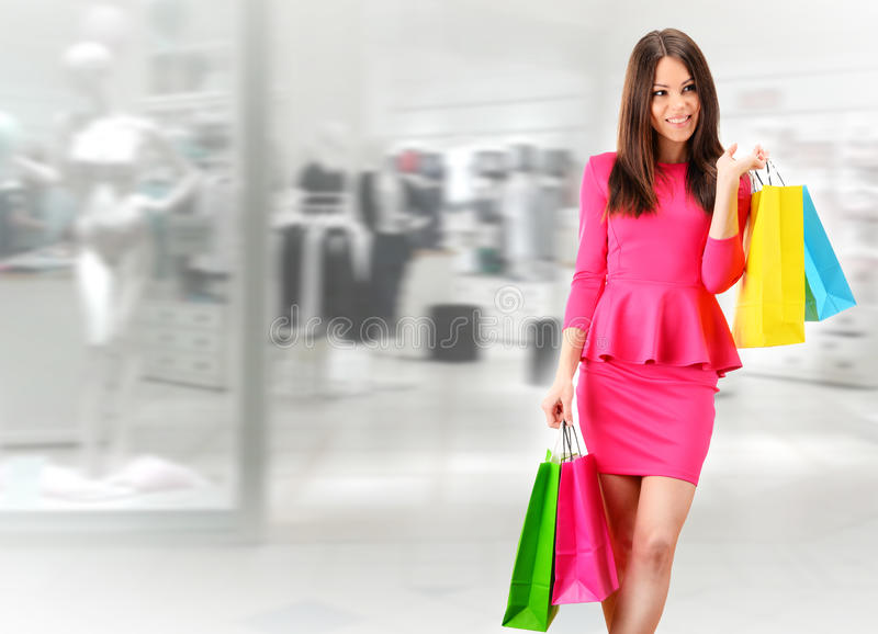 Young woman with bags in shopping mall stock photos