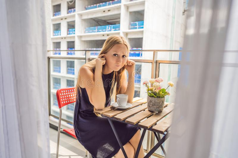 Young woman on the balcony annoyed by the building works outside. Noise concept. Air pollution from building dust.  royalty free stock photos