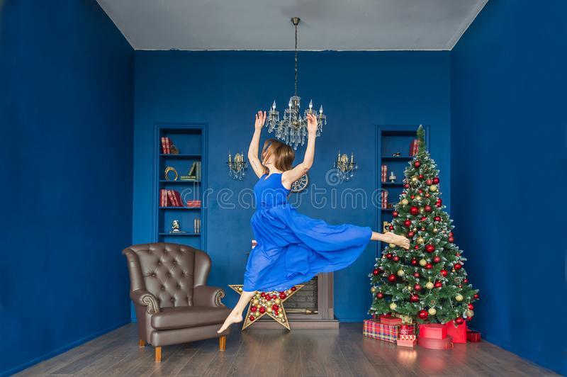 Young woman ballet dancer jumping in blue dress in a festive New Year`s interior stock photo