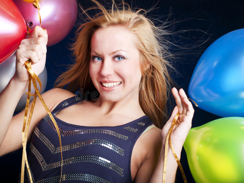 Young woman with ballons over dark. Smiling young woman with sylvester champagne over dark background royalty free stock images