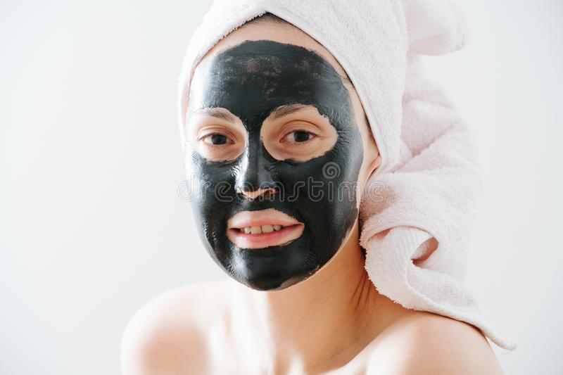 Young woman with bamboo peel off charcoal facial mask. Young clean woman after shower with bamboo charcoal peel off facial mask wearing towel on her head stock photos