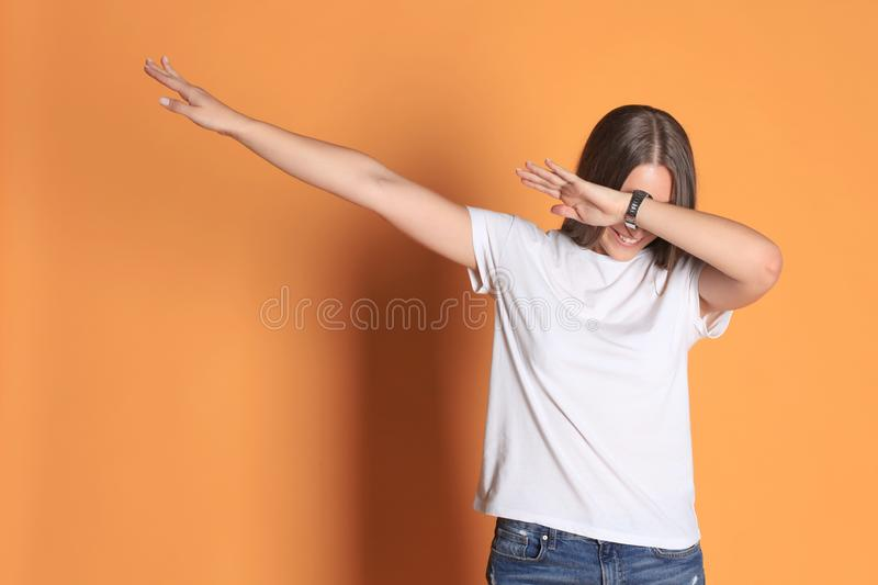 Young woman in basic clothing throws dab isolated on yellow background. Young woman in basic clothing throws dab isolated on yellow background royalty free stock image