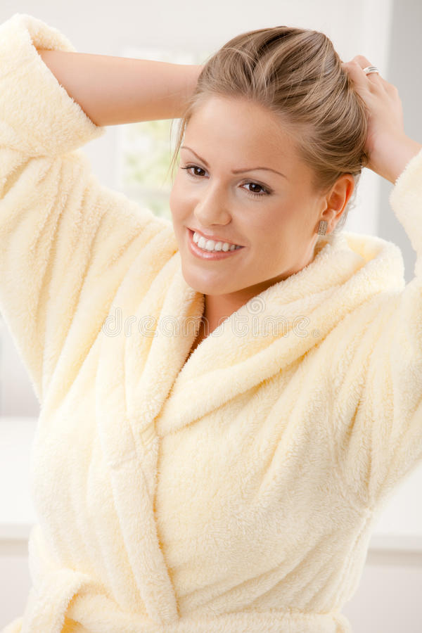 Young woman in bathrobe. Portrait of happy young woman wearing yellow bathrobe, smiling royalty free stock photo