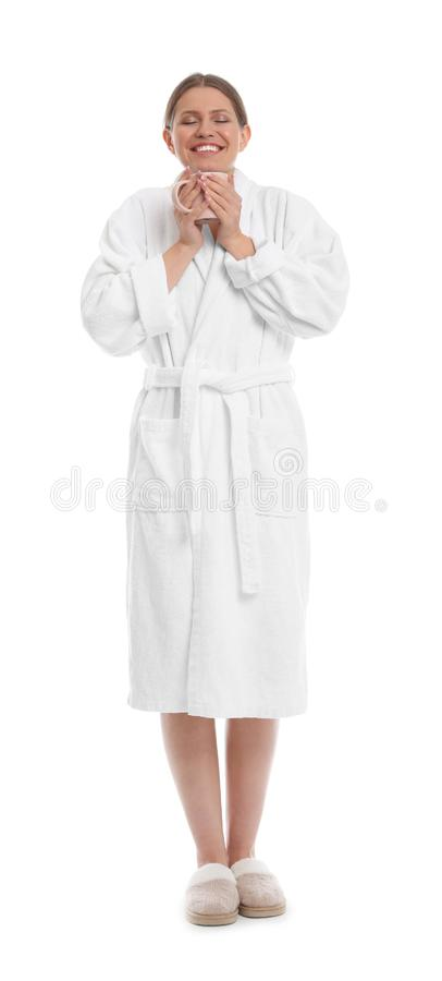 Young woman in bathrobe with cup of beverage on background royalty free stock photo