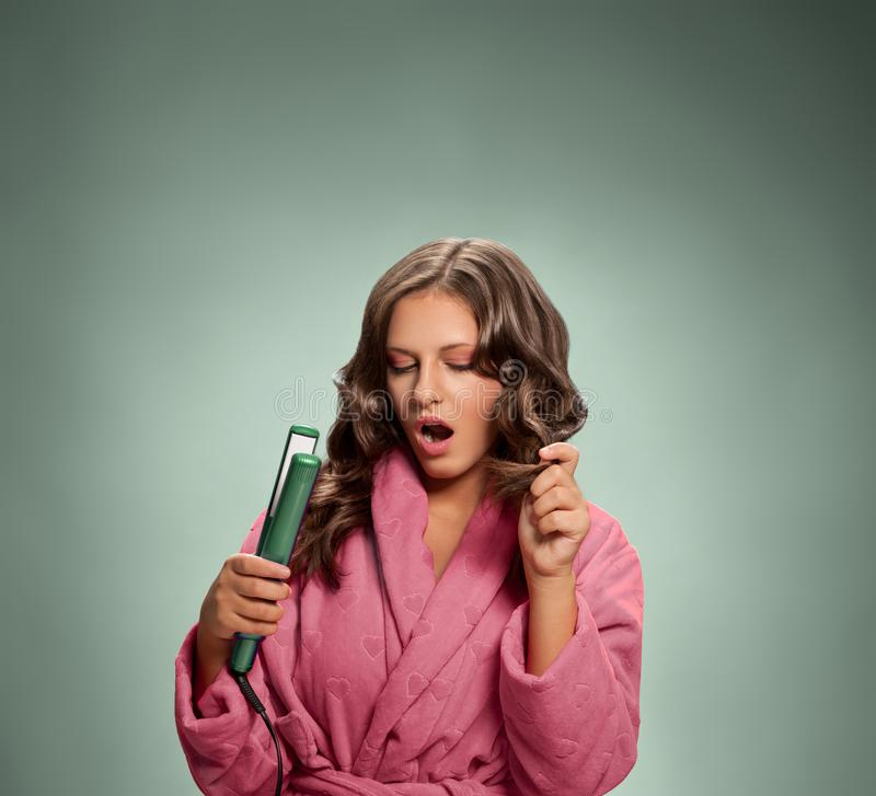Young woman in bathrobe holding hair iron royalty free stock photo
