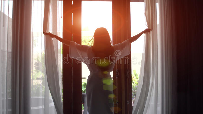 Young woman in bathrobe open curtains and stretch standing near the window at home. royalty free stock image