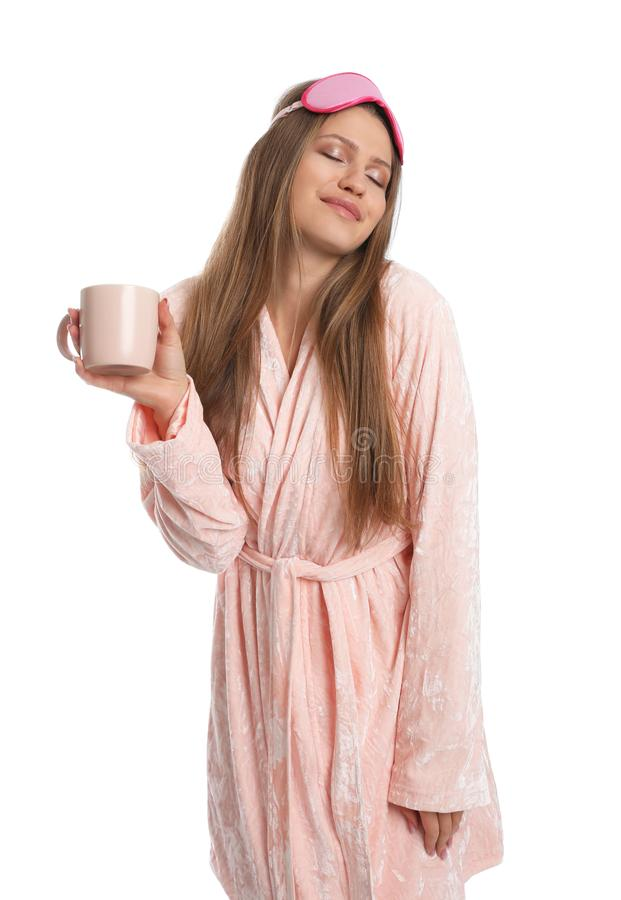Young woman in bathrobe with sleep mask and cup of beverage on background stock images