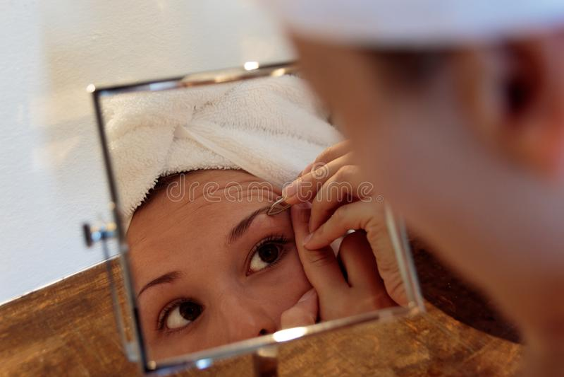 Young woman in bathroom. eyebrow depilation with tweezers stock image