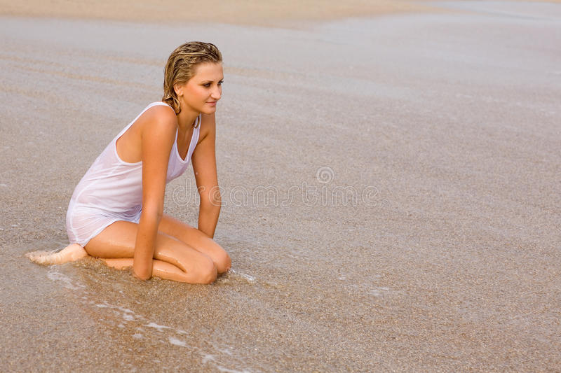 Young woman on the beach. A young woman on the beach by the sea stock photography