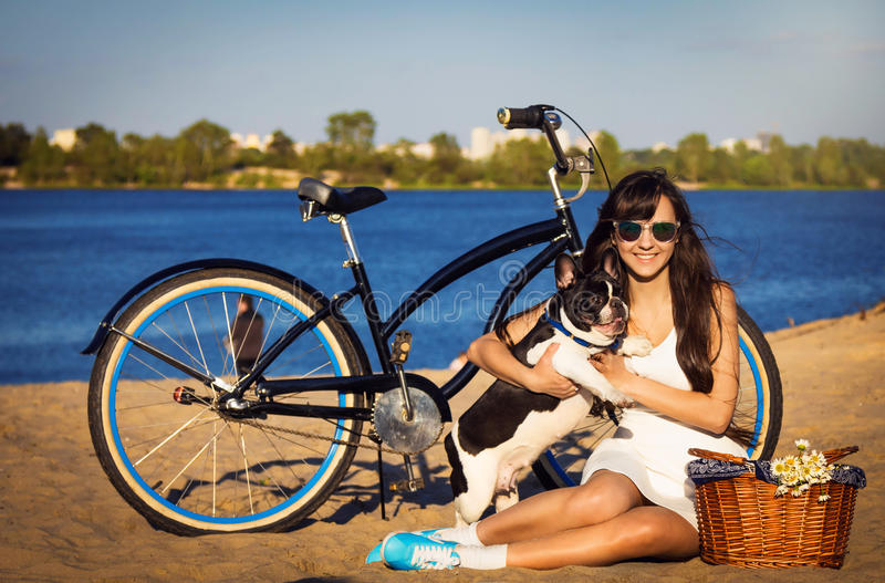 Young woman on the beach with bicycle and french bulldogs. Beautiful young girl sitting on the beach with bicycle and playing with french bulldogs stock photo