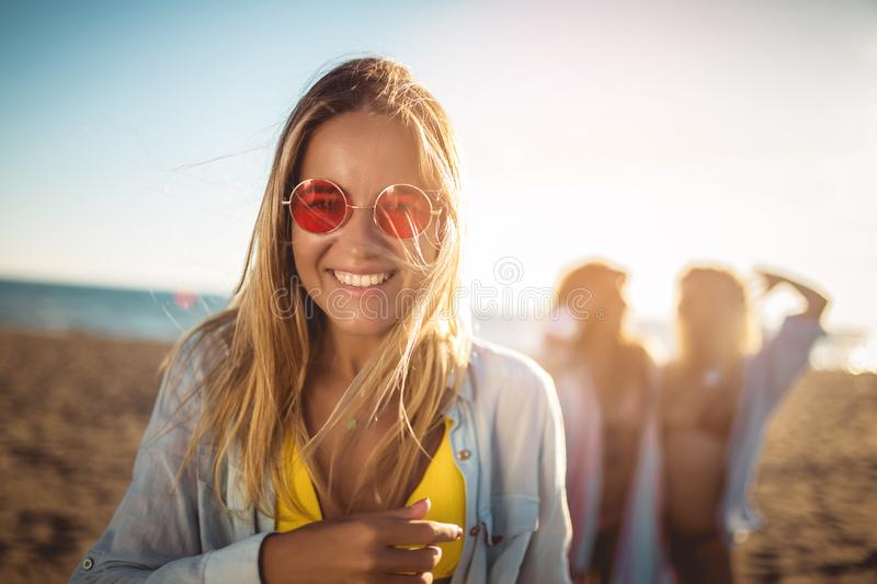 Young woman on the beach with her friends in background. Group of friends enjoying on beach holiday royalty free stock photo