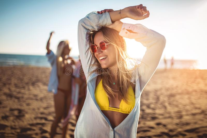 Young woman on the beach with her friends in background. Group of friends enjoying on beach holiday royalty free stock image