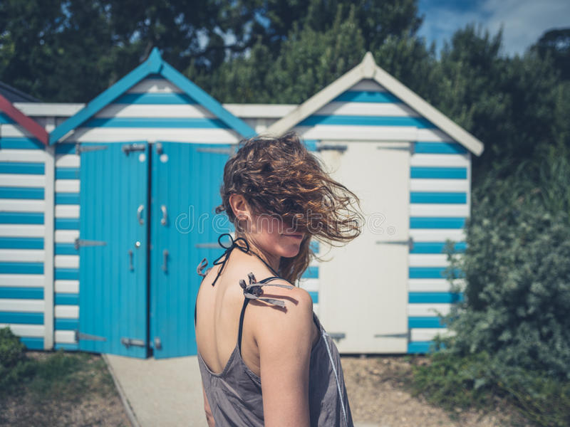 Young woman by beach huts. A young woman with wind swept hair is standing by some beach huts royalty free stock image
