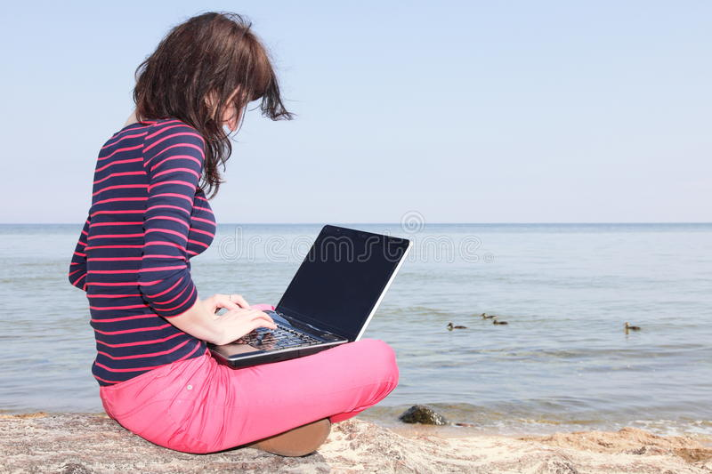 Young woman on the beach with a laptop. Young woman sitting and working at the beach with her laptop royalty free stock photography
