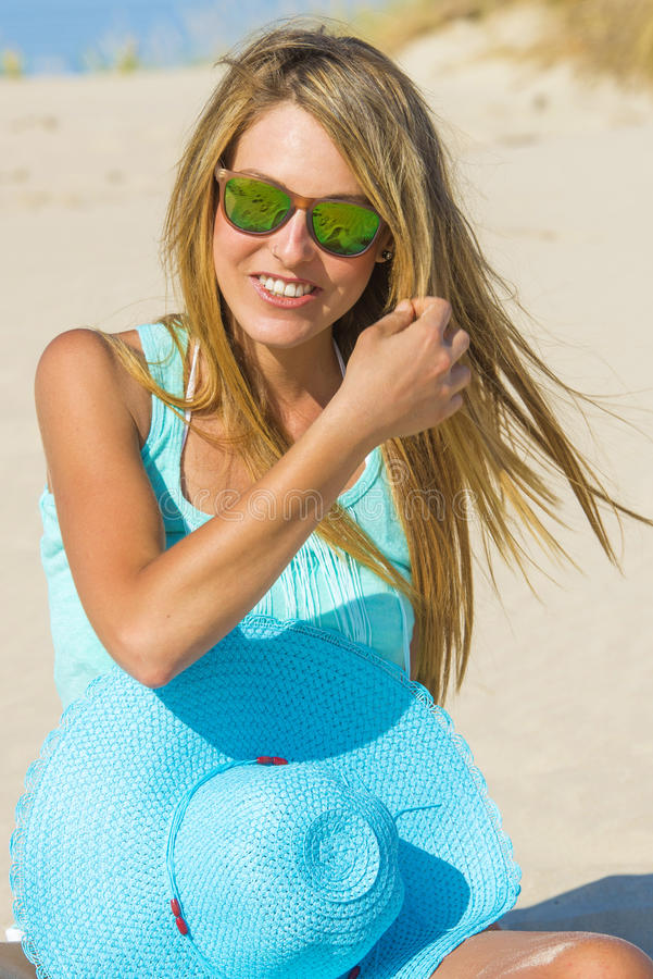 Young woman on the beach with pamela and blue shirt royalty free stock photos